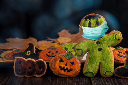 Ginger biscuits with face mask for Halloween holiday on wooden, concept of covid hallowen