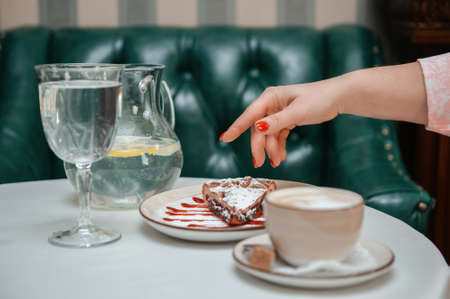 Closeup photo of female hands is reaching out to cake with cup of coffee in restaurant