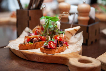Tasty tomato Italian bruschetta on toasted slices of baguette with spice herbs and basil on a wooden board. Catering concept