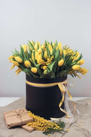 Bright spring bouquet of tulips and mimosa flowers. Mothers Day or Easter theme.