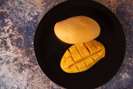 Fresh yellow mango fruit in a black plate