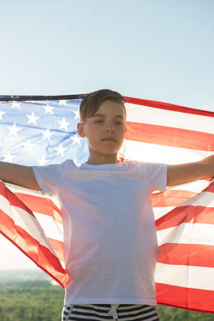 Blonde boy waving national USA flag outdoors over blue sky at the river bank