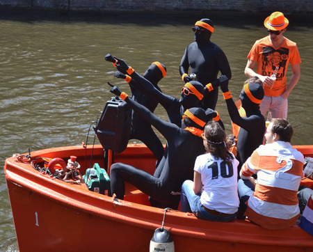 queen's birthday: Dressed in costumes of the artists in Amsterdam boat ride people in honor of the Queens birthday. Netherlands