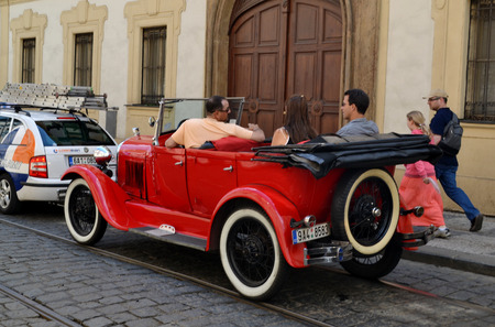 communicates: Prague Czech Republic May April 2012: Retro Convertible on the roads of Prague. In the streets of the city goes retro car with passengers. The driver communicates with clients.