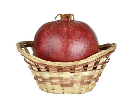ripe pomegranate in the basket isolated on a white background