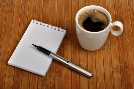 notebook with a pen and a cup of coffee