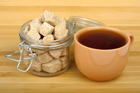 tea and cane sugar in the pot on a wooden background