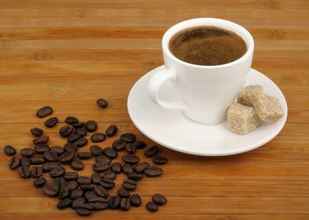 coffee, sugar cane and coffee beans on a wooden background