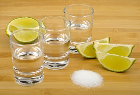 tequila, lime and salt on a wooden background