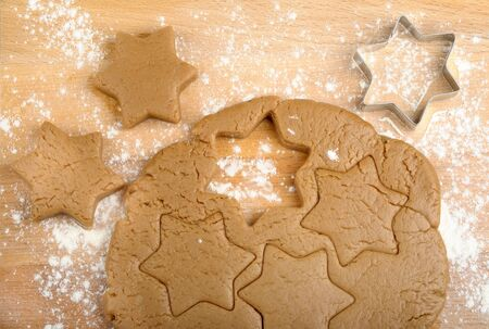 dough and cookie cutter on a wooden background photo