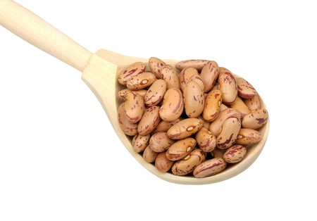 Pinto beans in wooden spoon isolated on white background photo