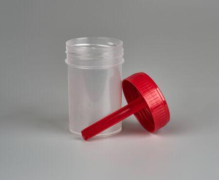 Recipiente para biomaterial con cuchara sobre fondo gris
