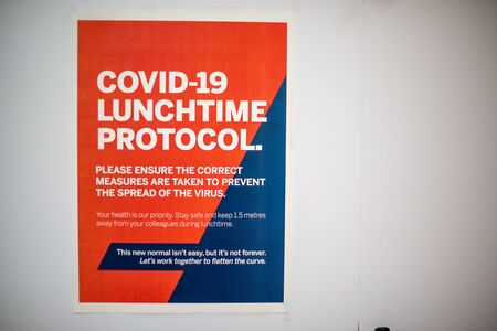 Covid-19 lunchtime protocol sign against wall at business Archivio Fotografico