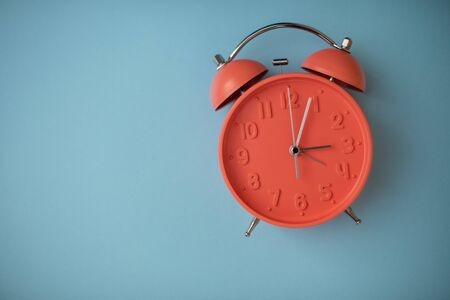 Clock isolated against solid background with copy space