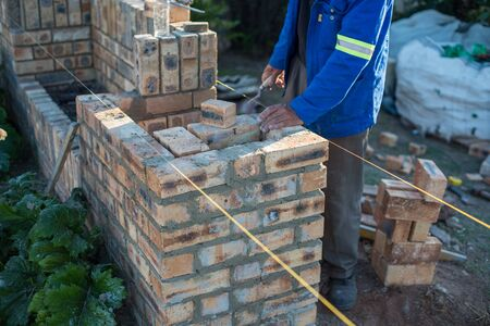 Cropped shot of worker laying bricks for wall