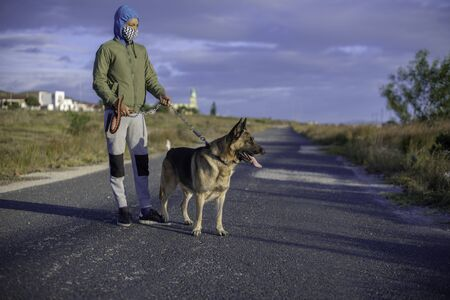 Young boy with mask taking his german shepherd for a walk