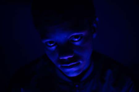 Close up portrait of teenager in dark room Banco de Imagens