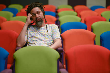 Single person sitting inside theatre with colorful seats