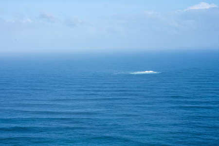 Landscape of ocean with whirlpool seen in distance