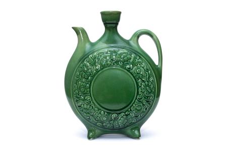 Green glazed ceramic jug on white background