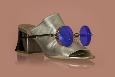 Womans shoe with sunglasses in a funny background Фото со стока
