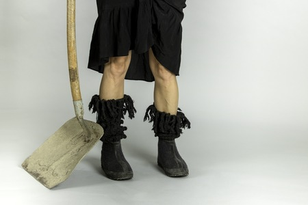 Woman in black shoes and shovel on gray background