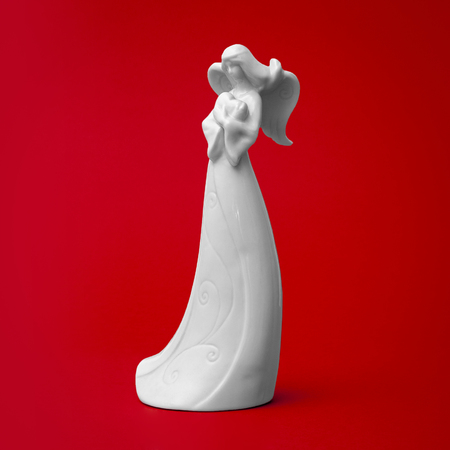 White porcelain angel sculpture with a heart in her hands in a bright red background