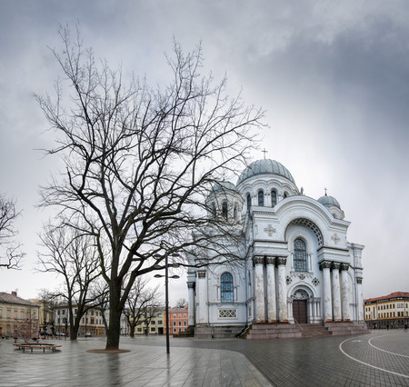 White church facade with a tree in Kaunas city on a cloudy spring day