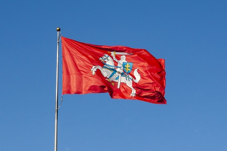 National bright red Lithuanian flag with a rider on a blue sky background
