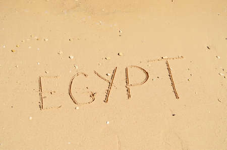 word Egypt written on sand