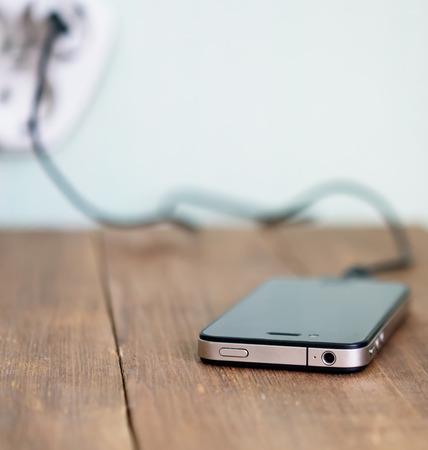 het opladen van mobiele telefoon op houten tafel Stockfoto