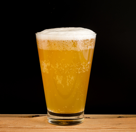 Full glass of beer on a black