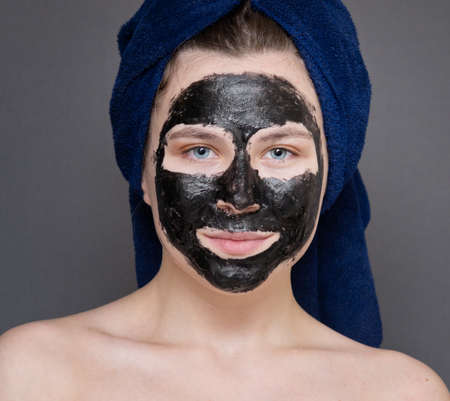 Young woman with cosmetic facial mask