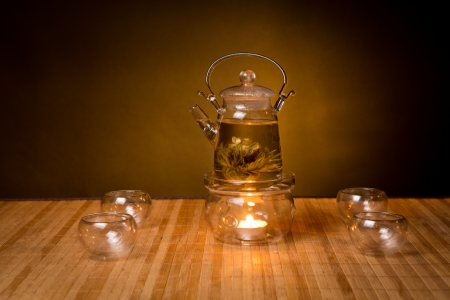 glass teapot with exotic green tea on wooden table on brown background photo