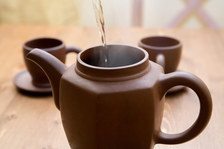 Clay teapot and cups on a wooden table