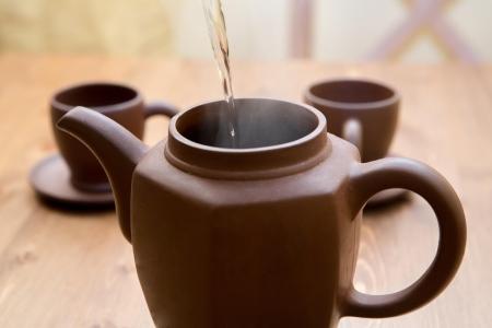 Klei theepot en kopjes op een houten tafel