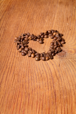 coffee beans in the form of heart on a wooden table photo