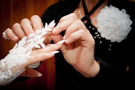 Friend help the bride to wear a glove
