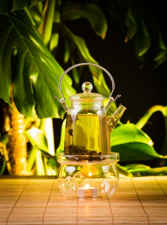 Chinese teapot with tea, on a burning support from glass Stock Photo