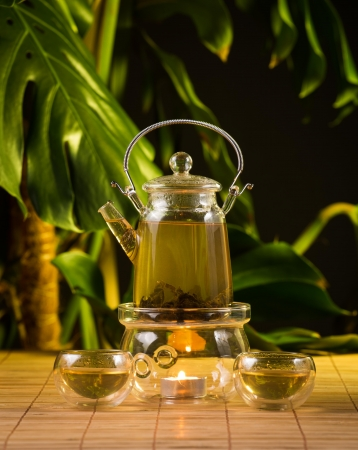 Chinese teapot with tea, on a burning support from glass photo