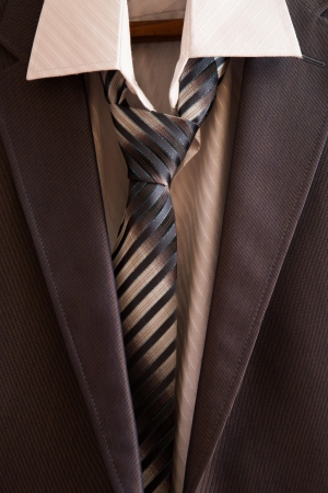 Business suit hanging on the rack in the wardrobe photo