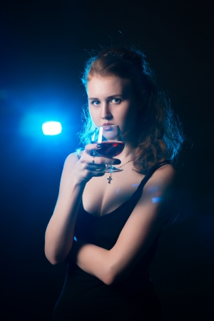 Glamour women with the wine on black background photo