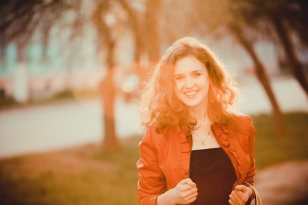 young curly Woman  smiling, on sunset photo