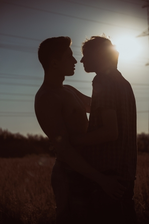 Silhouette of two men about to kiss