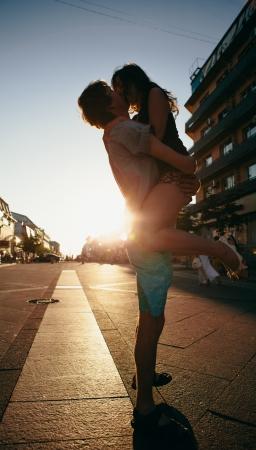 Het jonge paar kussen over zonsondergang