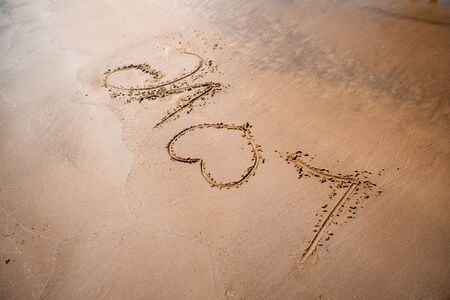 The word LOVE on sand.