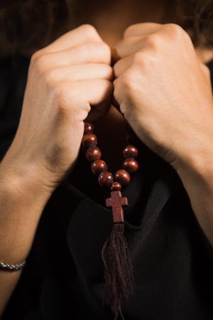 Close up shoot woman hands with rosary in dark background Stock Photo - 21276060