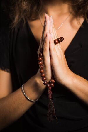 Close up shoot woman hands with rosary in dark background Stock Photo - 21276081