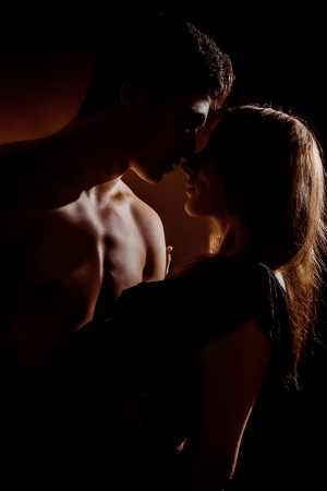 Beautiful young couple hugging and kissing isolated on black background. Stock Photo