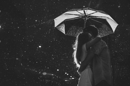 Man and the girl kiss in the rain. Photo contains glare from lights.